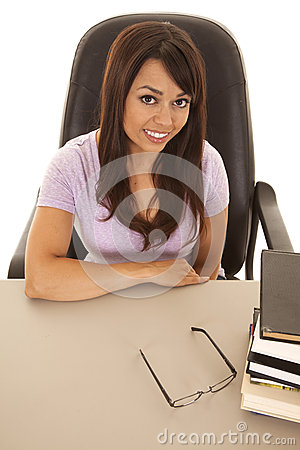 Woman at a desk with a stack of books top angle