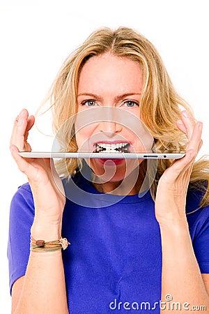 Woman with digital tablet between teeth