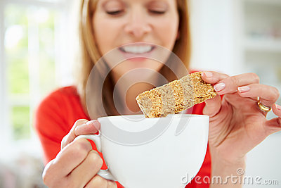Woman Dipping Biscuit Into Hot Drink At Home