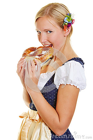 Woman in dirndl biting in a pretzel