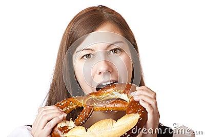 Woman in Dirndl eating Oktoberfest Pretzel