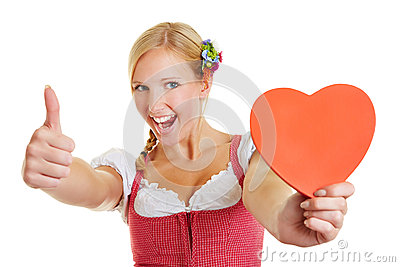 Woman in dirndl holding heart and thumbs up