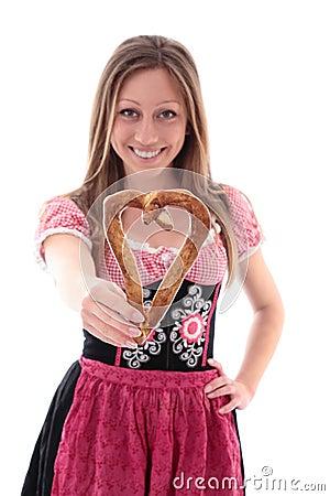 Woman in a dirndl holding a pretzel