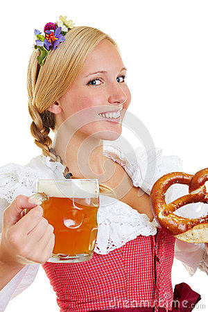 Woman in dirndl with pretzel and beer