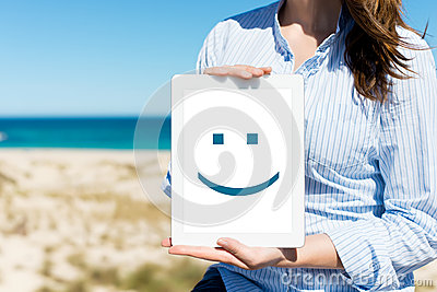 Woman Displaying Digital Tablet With Smiley Face At Beach