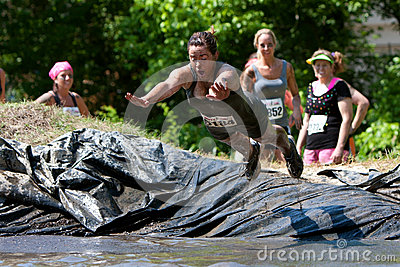 Woman Dives Into Mud Pit On Obstacle Course Editorial Image