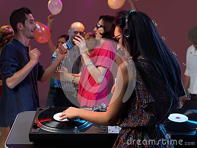 Woman dj entertaining crowd in night club