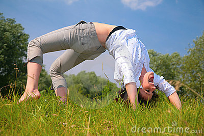 Woman does exercise on  grass