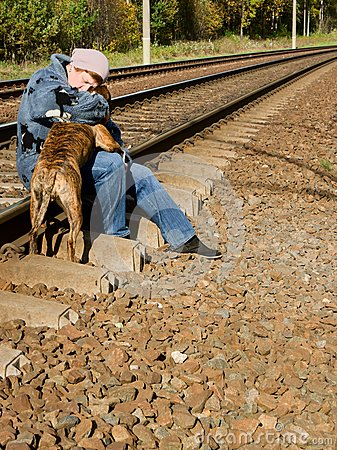 A woman with a dog on the railroad