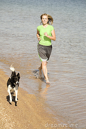 Woman and dog running in water