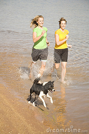 Woman and dog in water running
