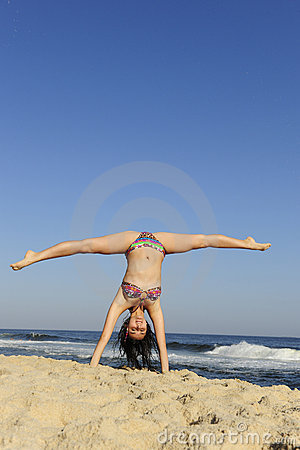 Woman doing acrobatics on beach