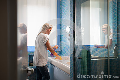 Woman doing chores and cleaning bathroom at home