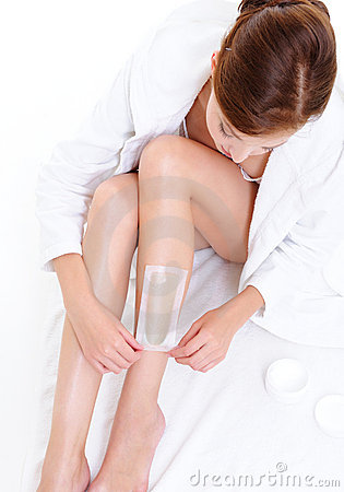 Woman doing depilation for her legs with waxing