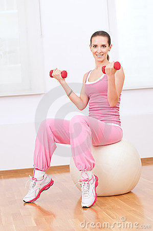 Woman doing dumbbell exercise at sport gym