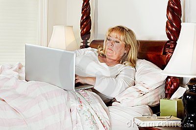 Woman doing e-mail in bed