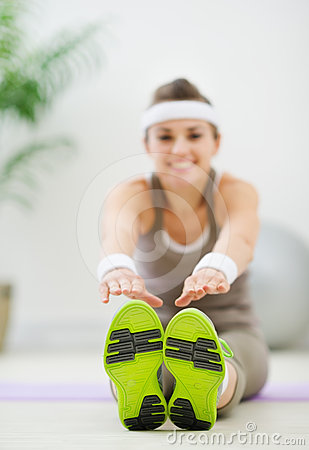 Woman doing exercises. Focus on sneakers