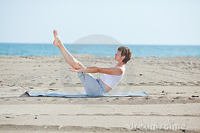 Woman doing fitness exercise on beach