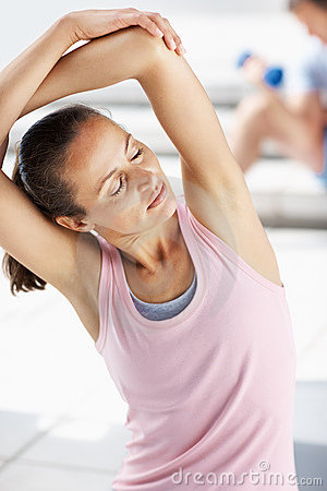 Woman doing hand stretch exercise at the gym