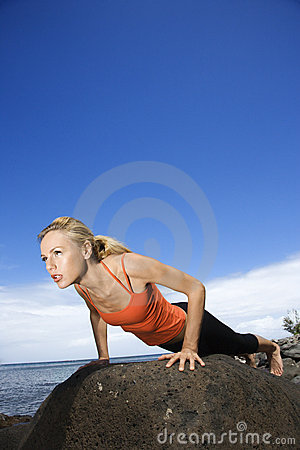 Woman doing push up on rock.