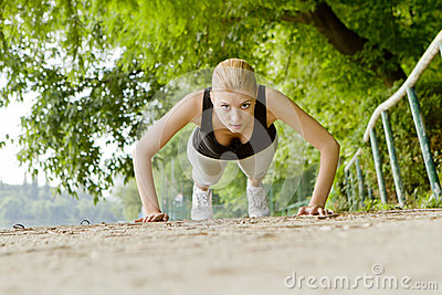 Woman doing push-ups outdoors