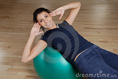 Woman doing sit ups with swiss ball