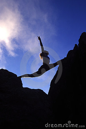 Woman doing splits on a mountaintop