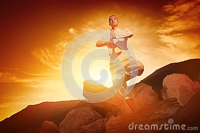 Woman doing yoga against sunrise