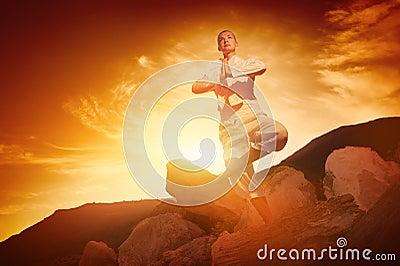 Woman doing yoga against sunrise