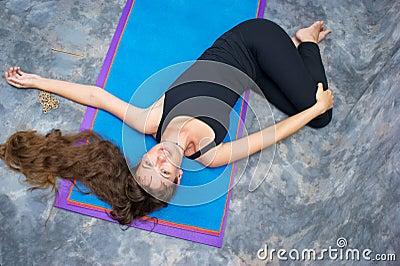 Woman doing yoga Ardha Jathara Parivarttanasa