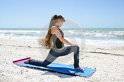 Woman doing yoga on beach Low Lunge