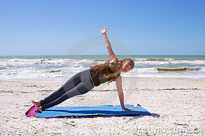 Woman doing yoga on beach in side plank