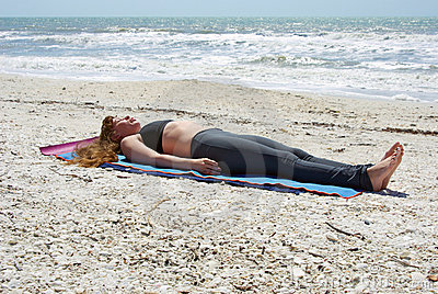 Woman doing yoga corpse pose on beach
