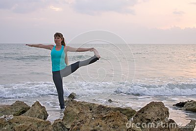 Woman doing yoga exercise at  beach