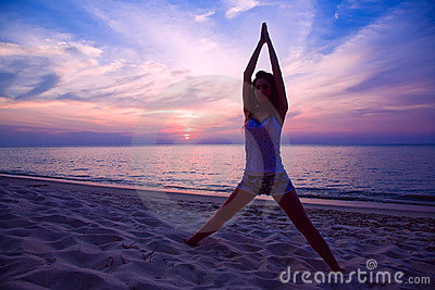 Woman doing yoga exercise on the beach