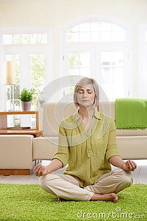 Woman doing yoga meditation at home