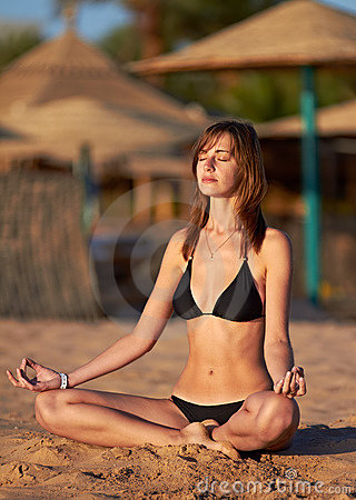 Woman doing yoga meditation in lotus on the beach