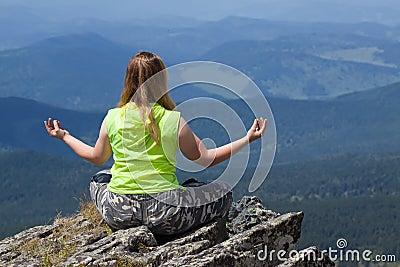 Woman doing yoga at mountain