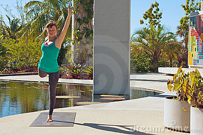 Woman doing yoga outdoors in dancer pose
