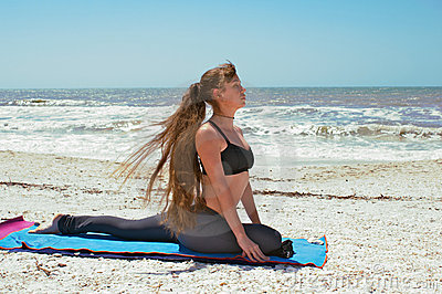 Woman doing yoga pigeon pose on beach