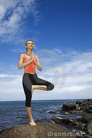 Woman doing yoga on rocky shore.