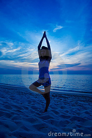 Woman doing yoga at the sunset beach