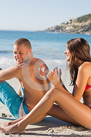 Woman drawing heart pattern with sun cream on her boyfriends bac