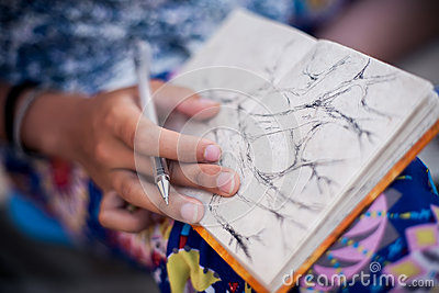 Woman drawing tree in her notebook