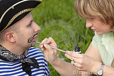 Woman drawing whiskers and beard on man s face