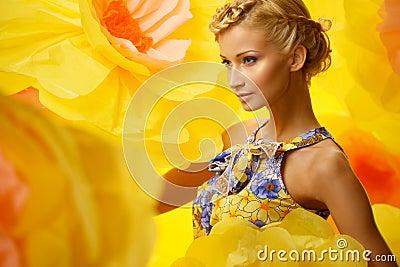 Woman in dress among big yellow flowers