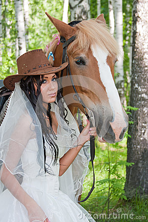 woman in the dress of fiancee next to a horse