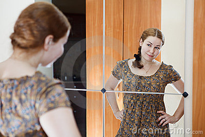 Woman in dress standing against mirror