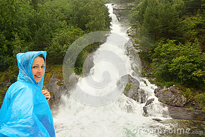 Woman dressed in raincoat stands near waterfall