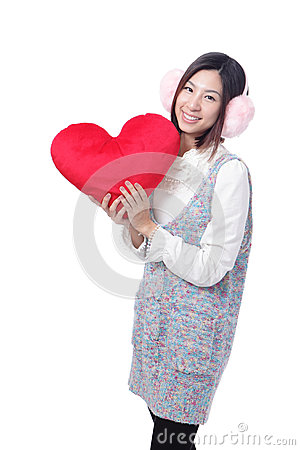Woman dressed in warm clothes with love pillow